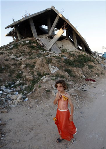In this June 1, 2009 file photo a Palestinian girl passes by a house destroyed during Israel's three-week offensive in Gaza earlier this year, in Jabaliya. (AP Photo/Khalil Hamra)