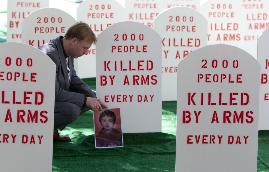 Control Arms campaigner David Grimason lays a photo of his son Alistair, who was killed by stray bullets in a gun fight, at the base of a mock tombstone. Control Arms coalition set up a mock graveyard next to the United Nations building in New York